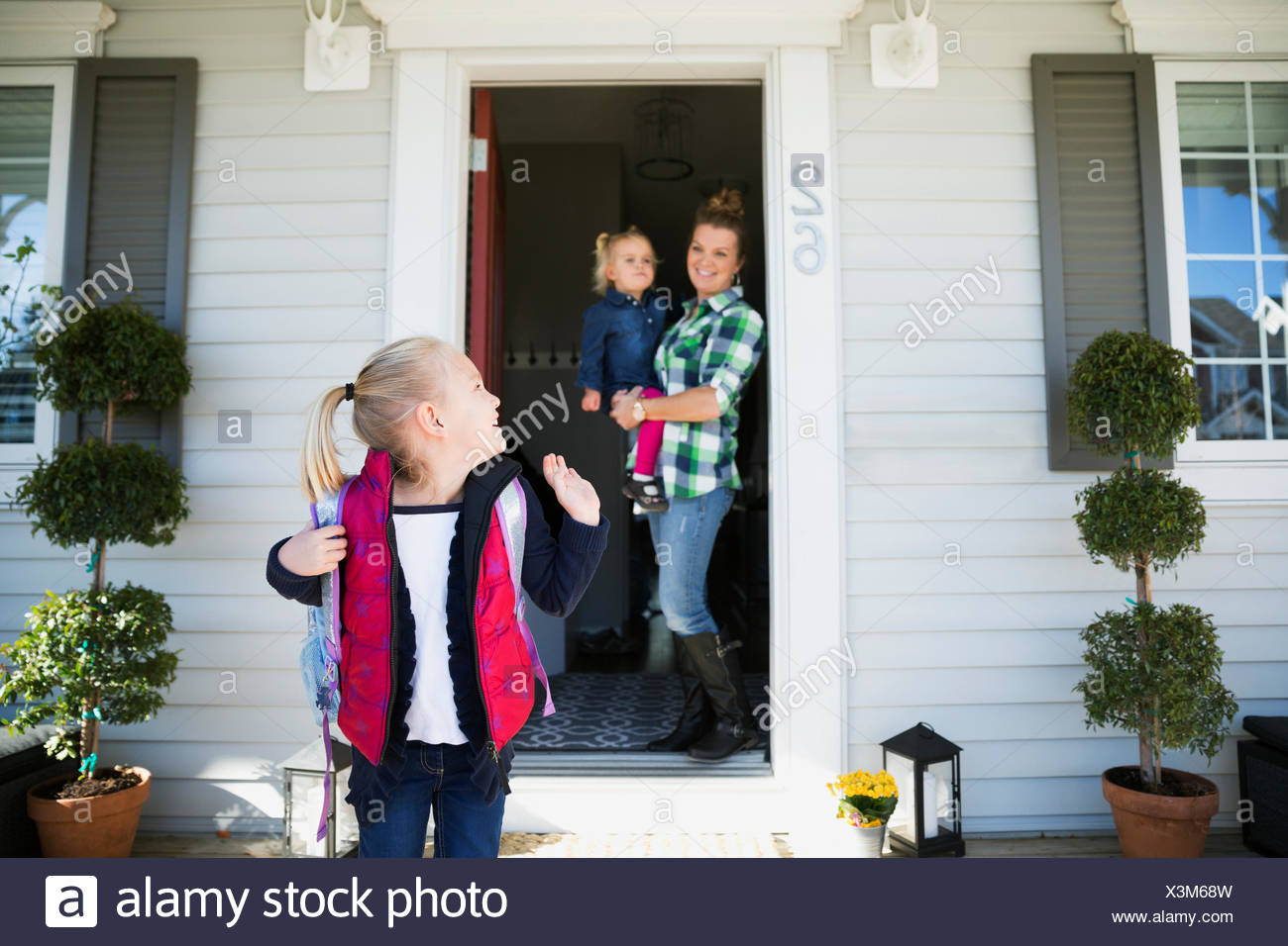 Daughter waving goodbye to mother sister front stoop - Stock Image
