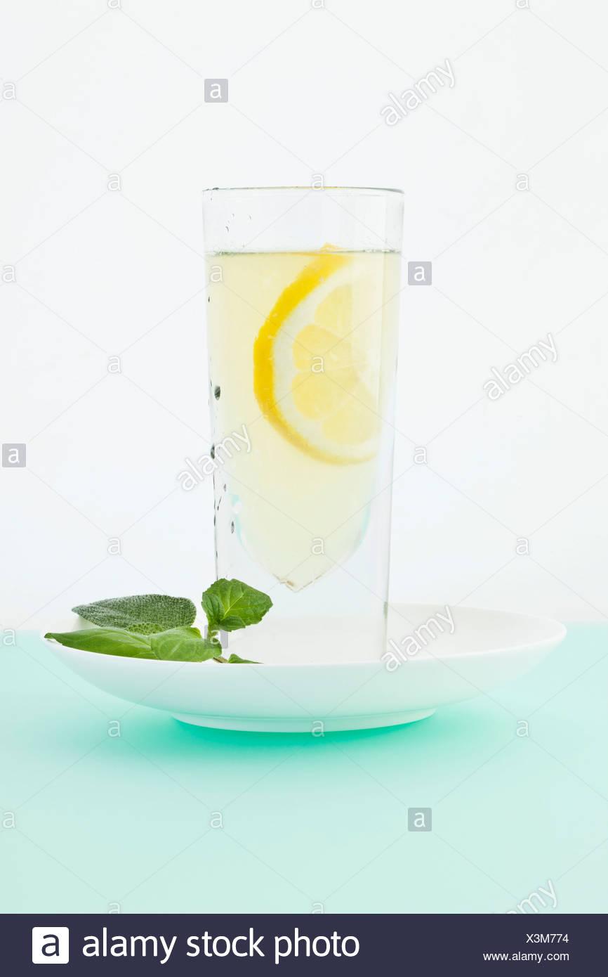 Lemonade with mint, sage and honey on coloured background - Stock Image