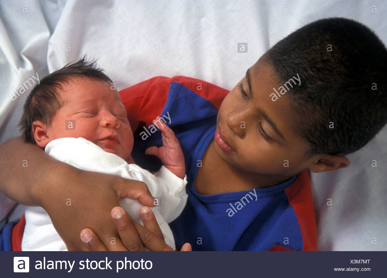 bi-racial young boy holding his newborn sibling - Stock Image