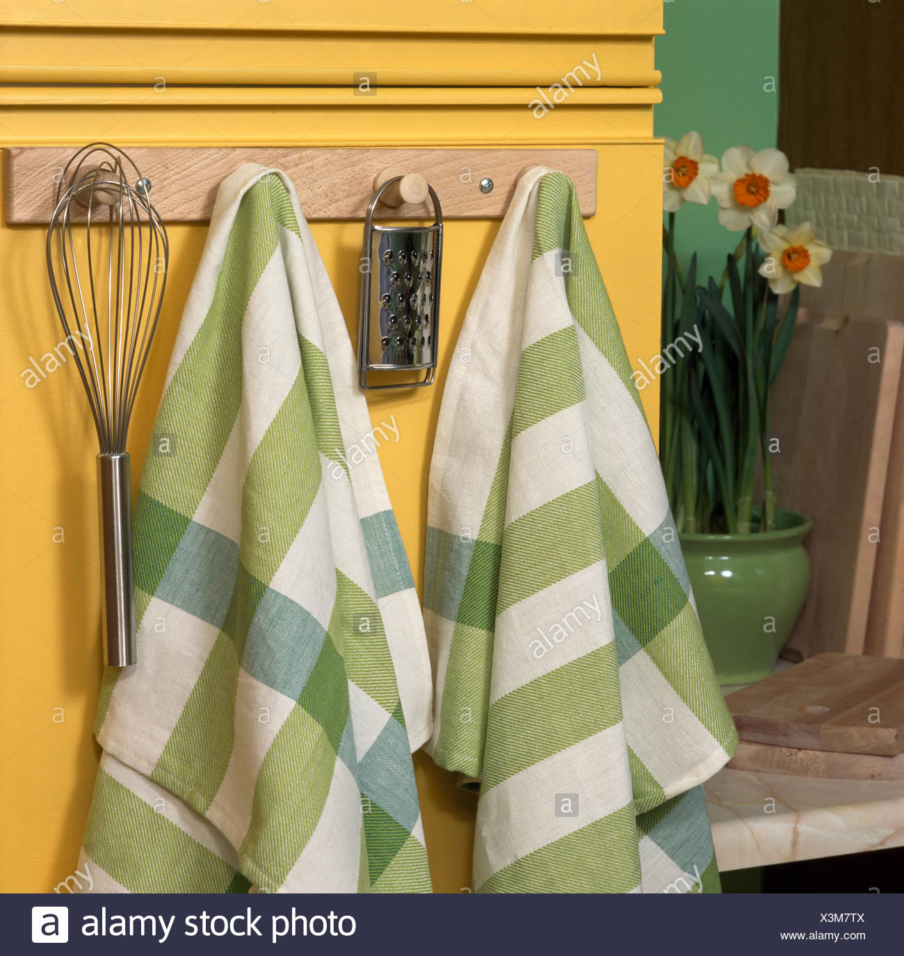 Close-up of green checked tea towels on a peg board with kitchen utensils - Stock Image