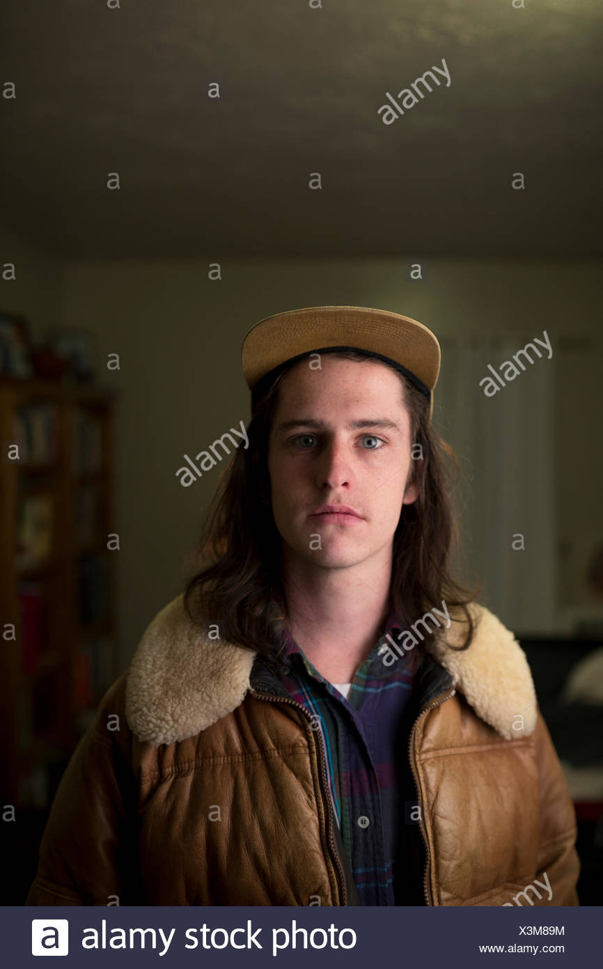 A young college boy poses wide-eyed in a home. - Stock Image