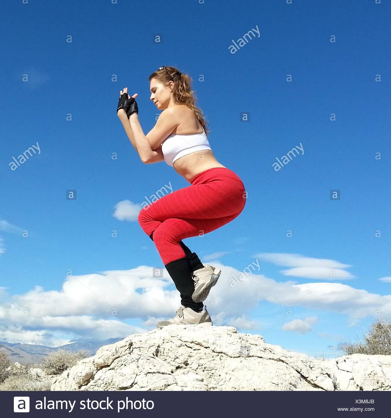 Woman doing an eagle yoga pose in the desert, Nevada, America, USA - Stock Image