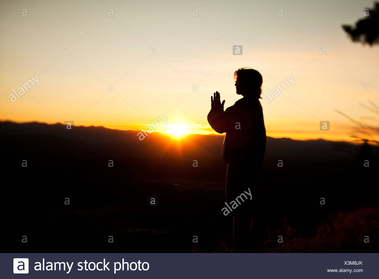 A young man praying as the sun rises over a valley in Idaho. - Stock Image