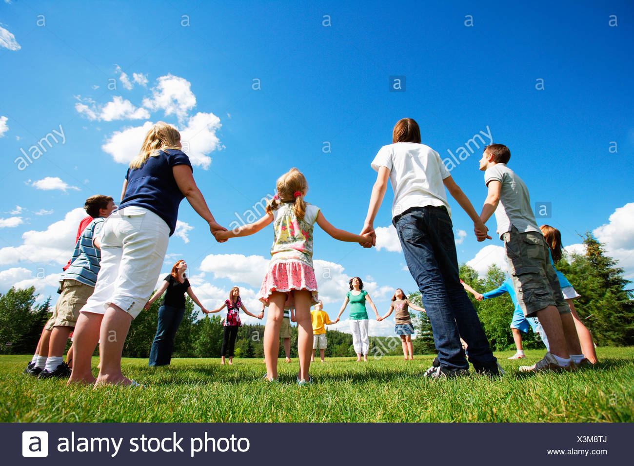 Holding hands in a circle - Stock Image