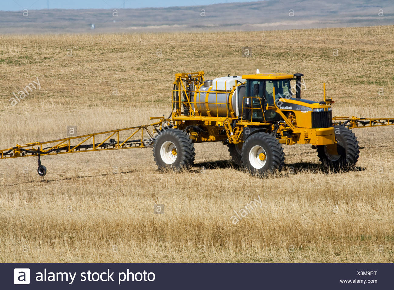 A RoGator applies herbicide to a dryland grain field in Spring prior to planting a new grain crop / Alberta, Canada. - Stock Image