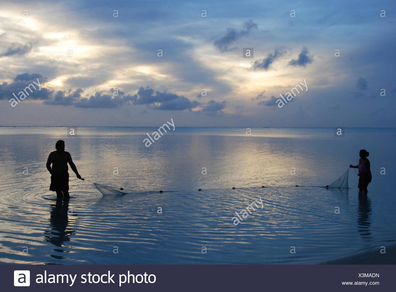 Fishermen at sunset, Aitutaki Atoll, Cook Islands, Pacific Ocean - Stock Image