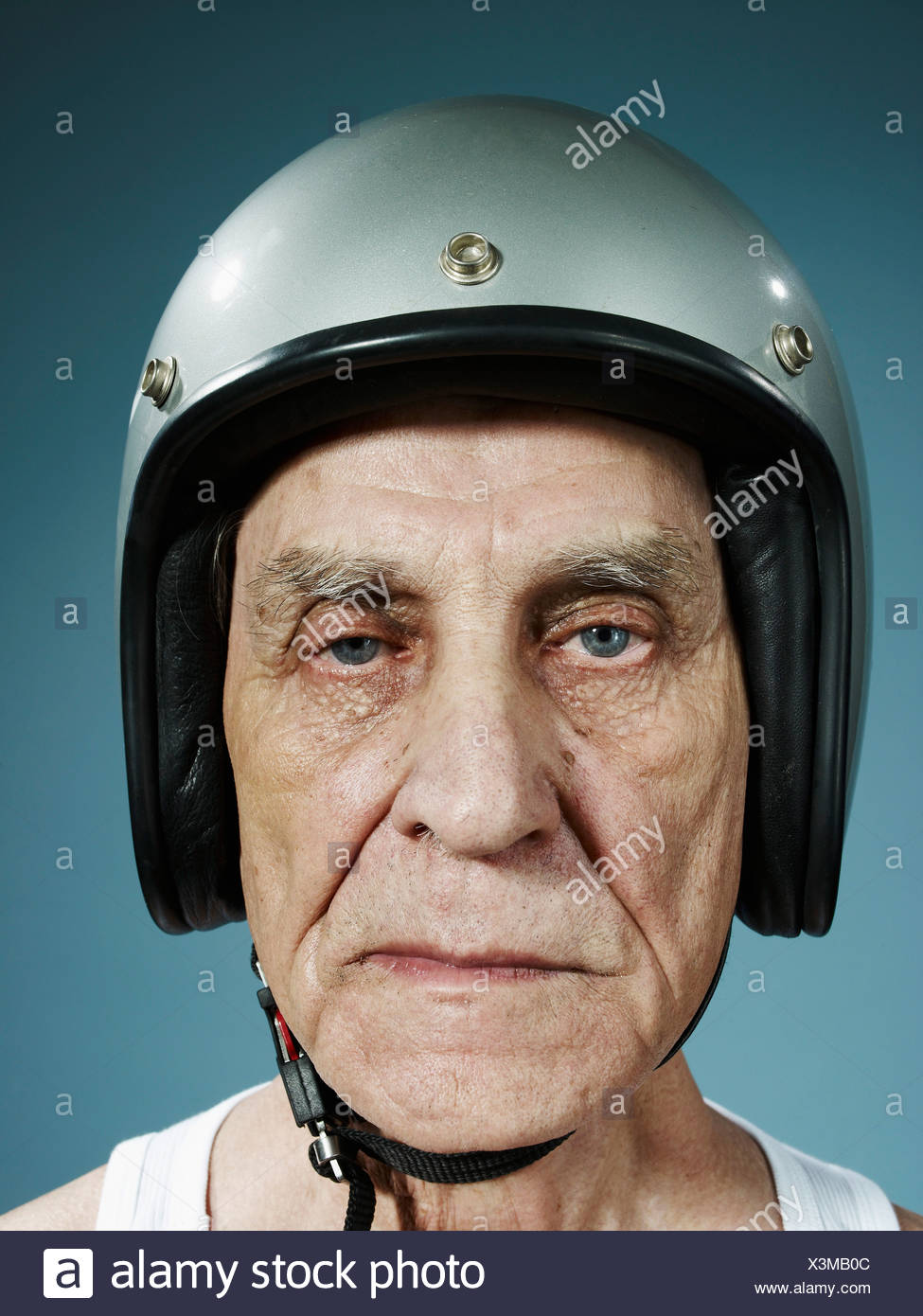 A headshot of a frowning senior man wearing a crash helmet - Stock Image