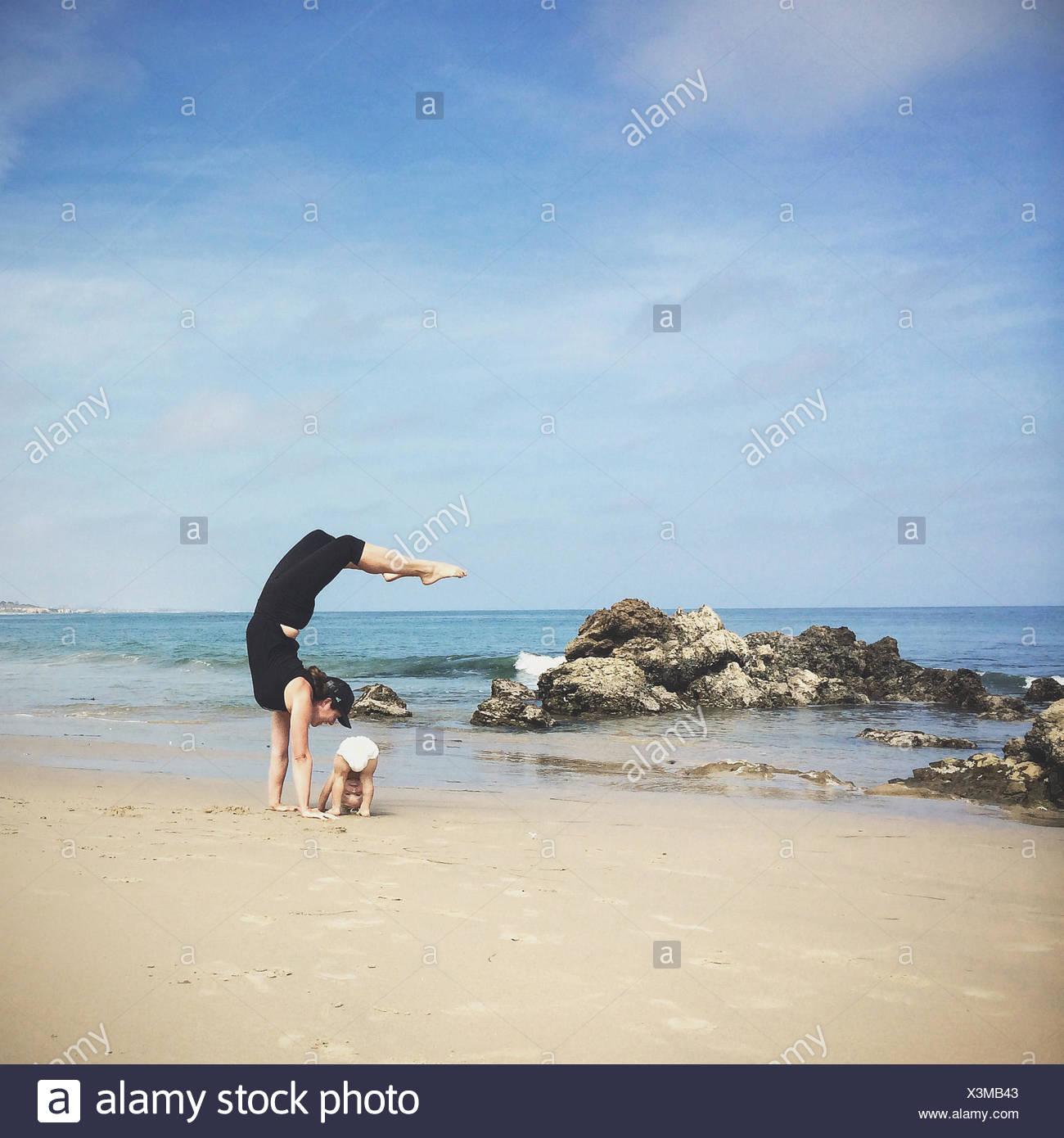 Mother and son doing yoga on beach, California, america, USA Stock Photo