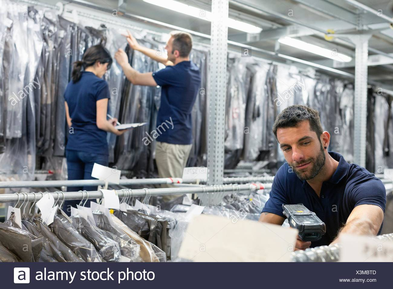 Three warehouse workers preparing garments in distribution warehouse - Stock Image