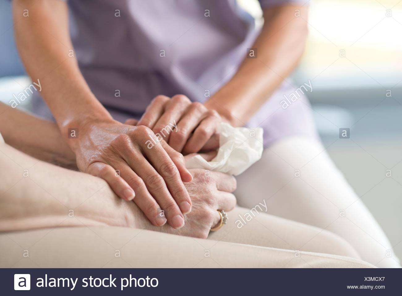 Care worker holding senior woman's hands. - Stock Image