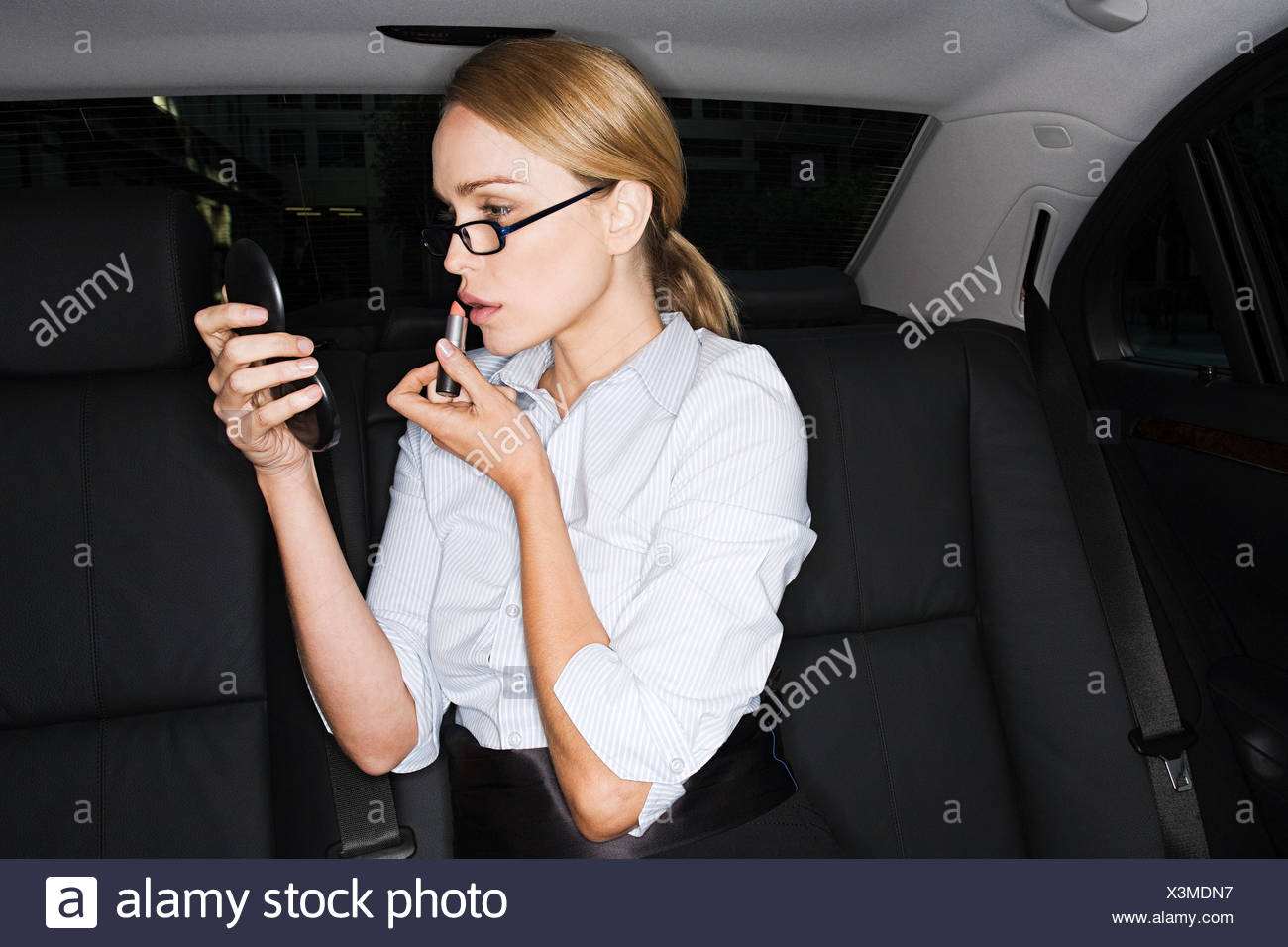 Businesswoman applying lipstick - Stock Image