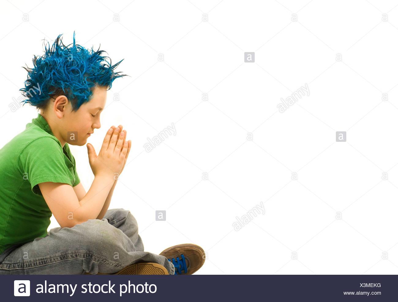 Blue haired boy praying - Stock Image