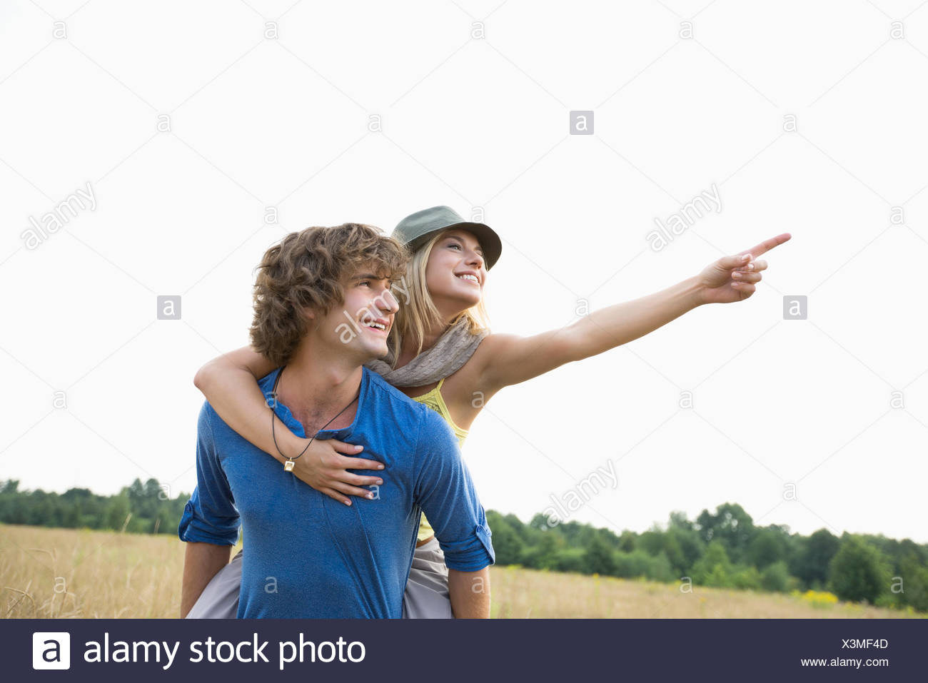 Happy woman showing something while enjoying piggyback ride on man in field Stock Photo