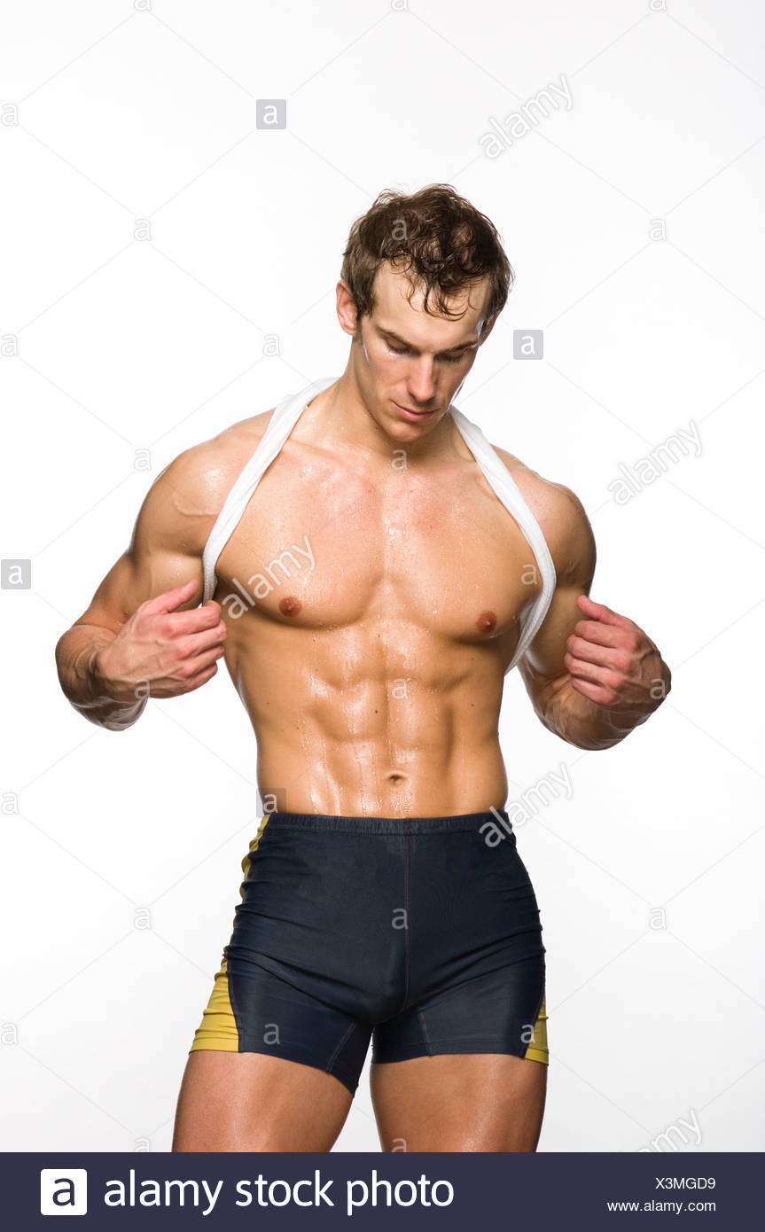 c7b08cbc5891 Muscular young man sweating and looking at abdominal muscle Stock ...