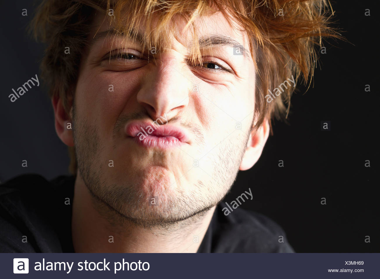Close up of young man with messy hair against black background, pouting, portrait - Stock Image