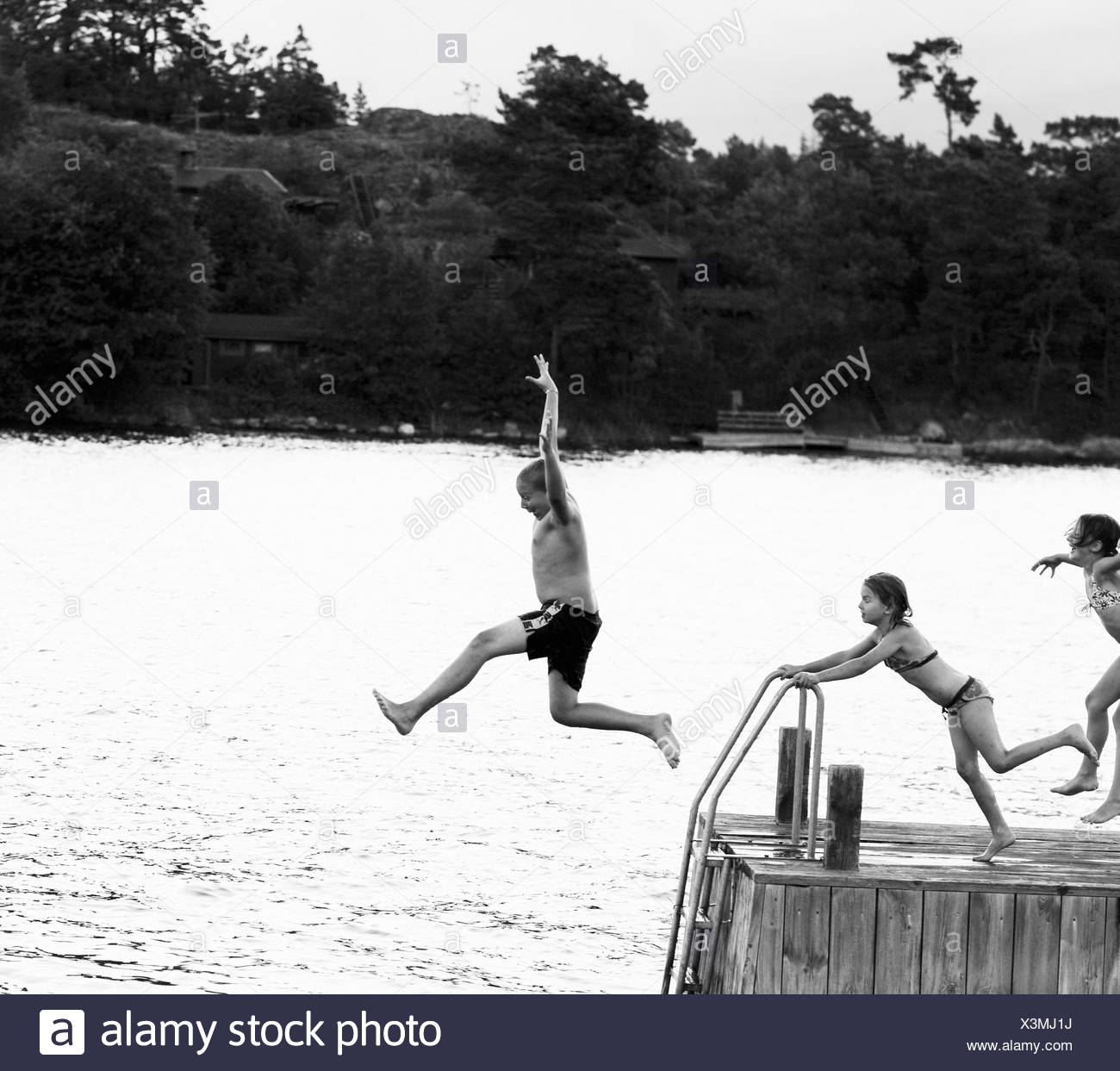 Three children jumping from a jetty Sweden. - Stock Image
