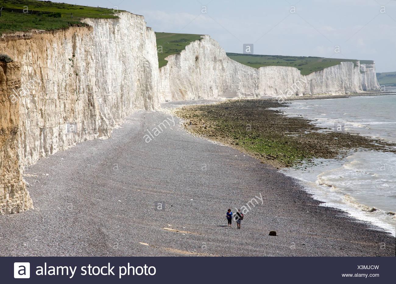 UK. England. Kent. Eastbourne. Chalk cliffs and couple walking along pebble beach. - Stock Image