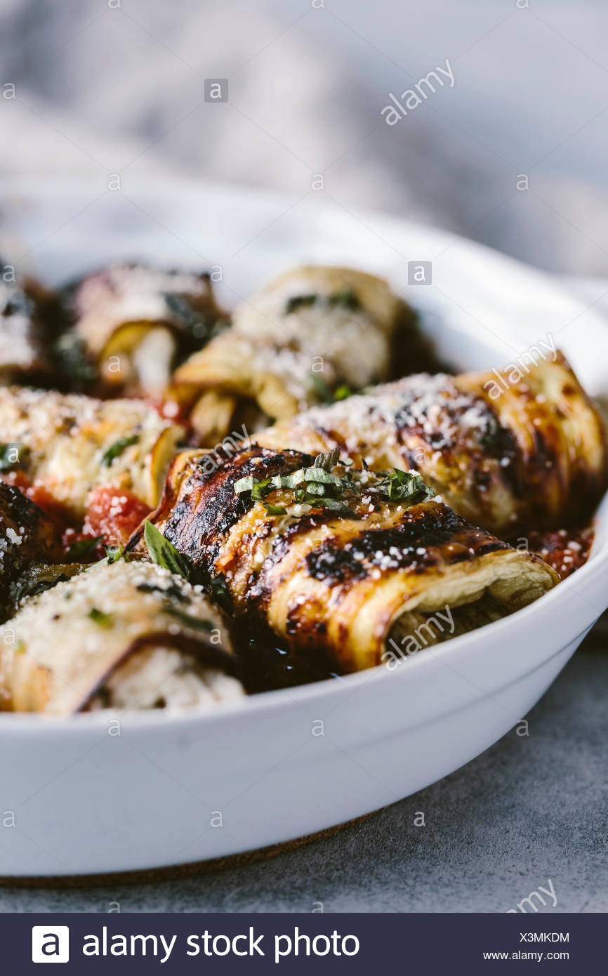 A large plate of eggplant involtini is photographed from the front view. - Stock Image