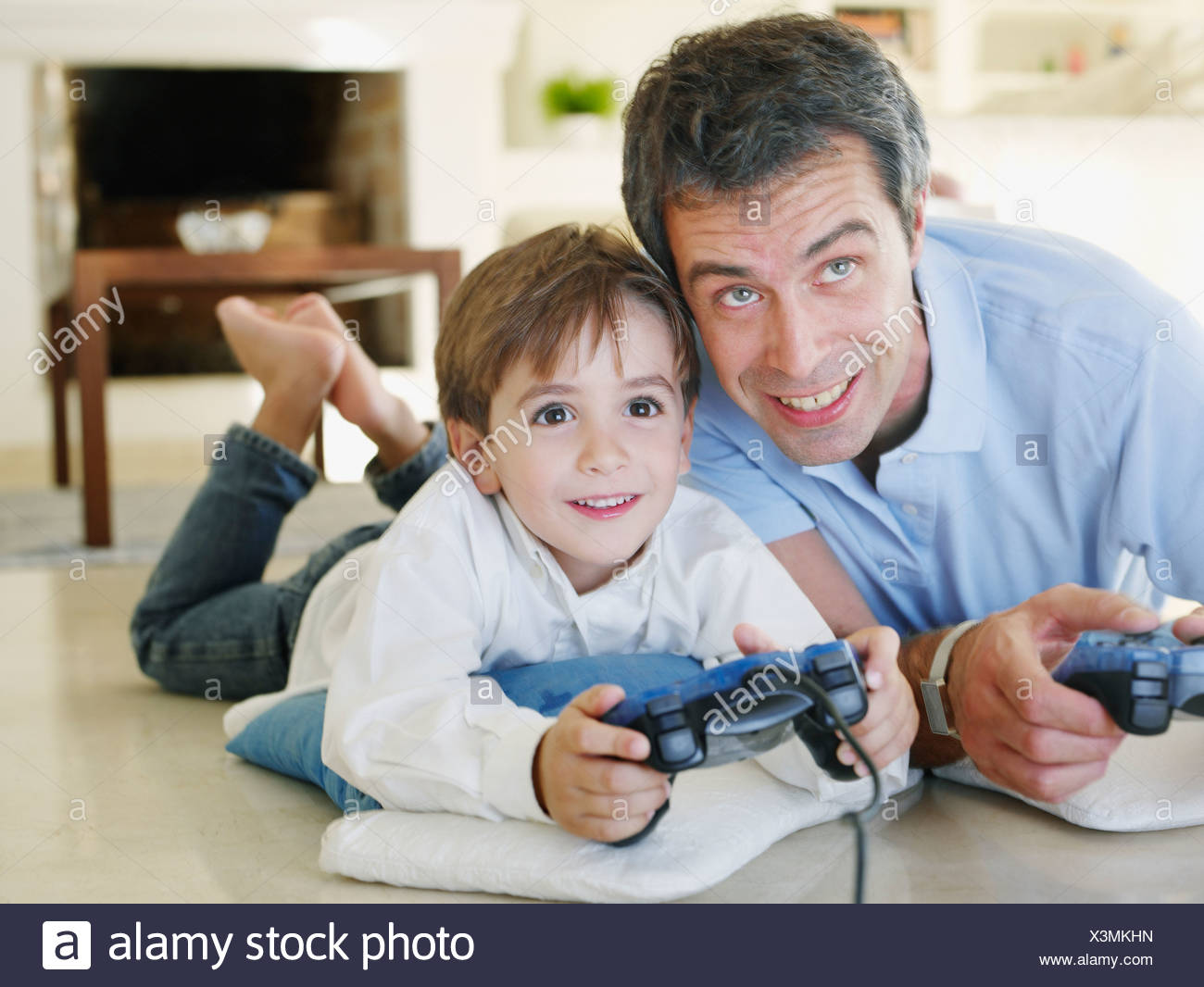 Father and son playing video game together Stock Photo