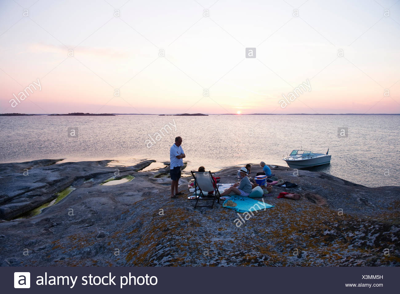 Sweden, Sodermanland, Stockholm Archipelago, Norsten, Scenic seascape with people picnicking - Stock Image
