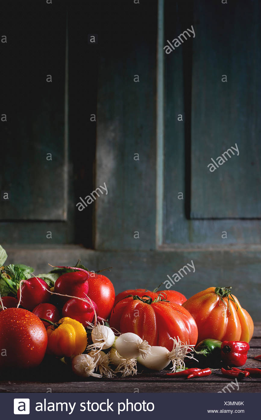 Heap of fresh ripe colorful vegetables tomatoes, chili peppers, green onion and bunch of radish over old wooden table. Dark rust - Stock Image