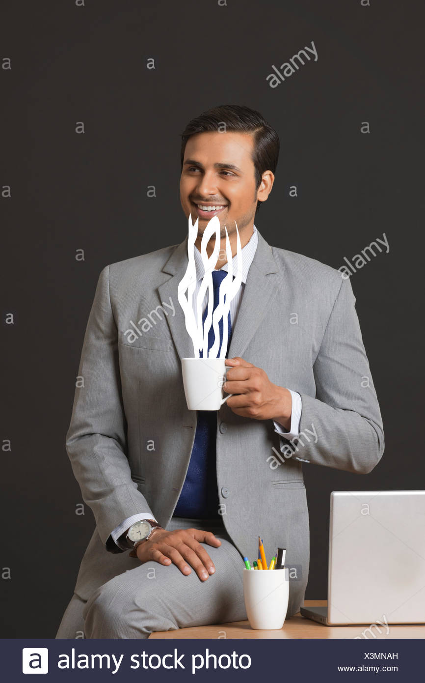 Digitally generated image of businessman having coffee in office - Stock Image
