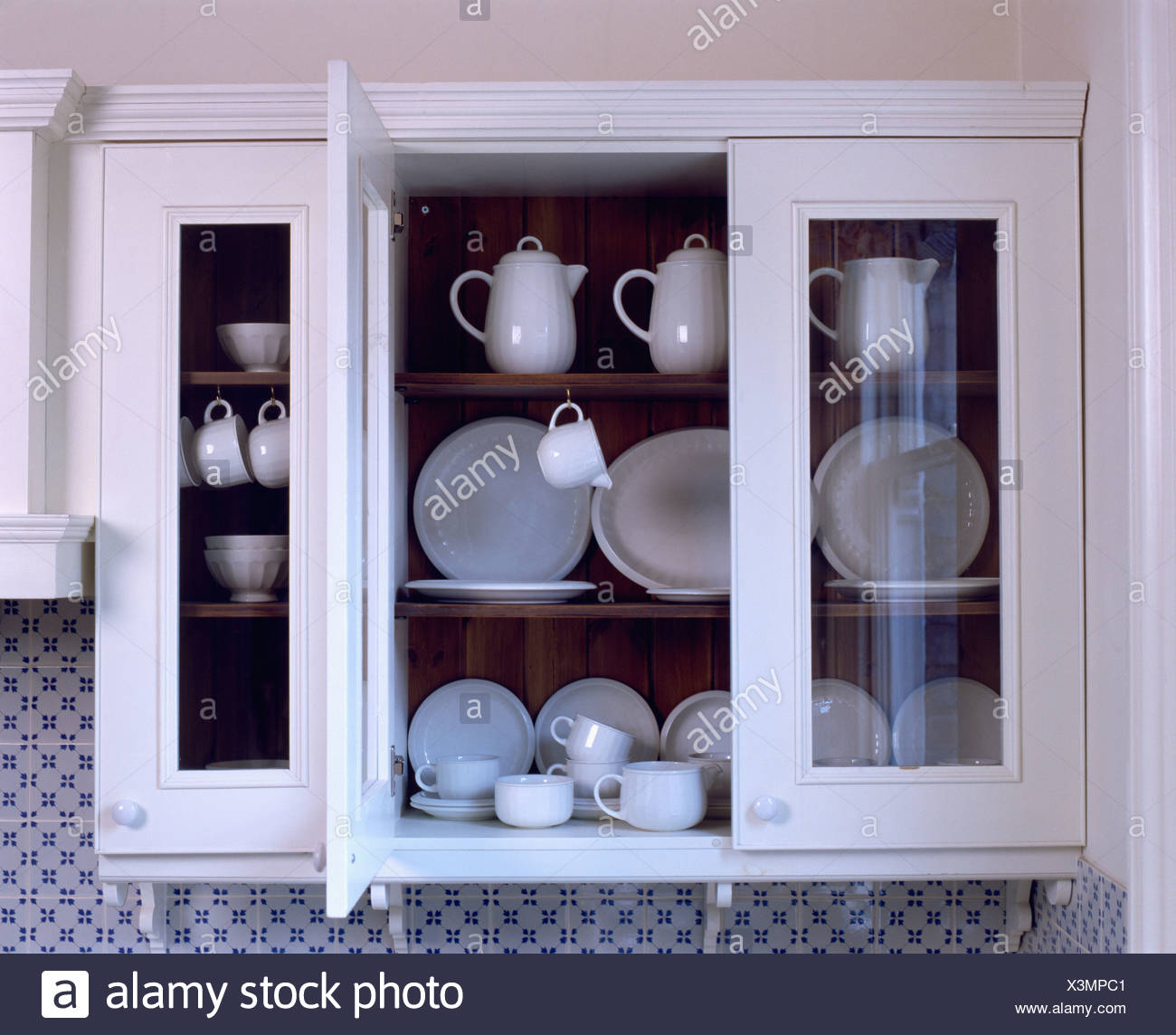 White Wall Cupboard With Glass Doors Open To Reveal White Crockery