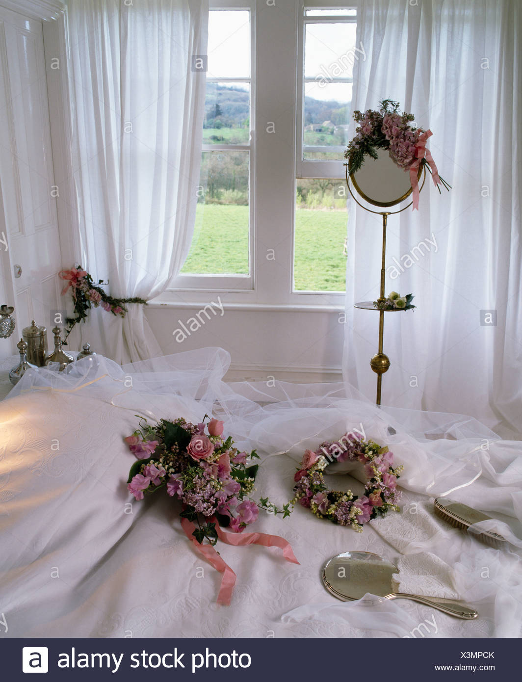 floral wedding head dresses and veil on white bed in front of window with white curtains in. Black Bedroom Furniture Sets. Home Design Ideas