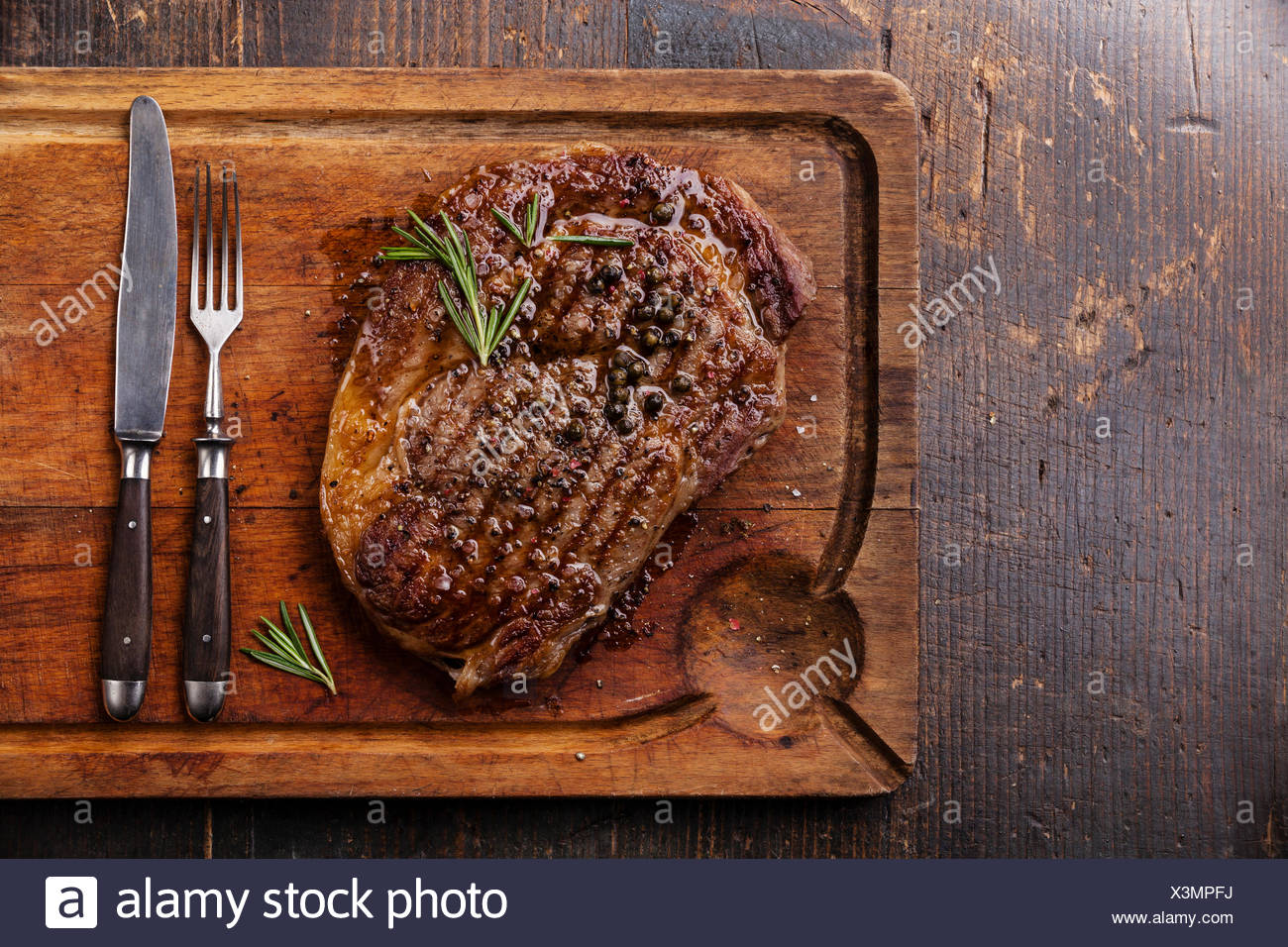 Grilled Black Angus Steak Ribeye and fork and knife on meat cutting board on dark wooden background Stock Photo
