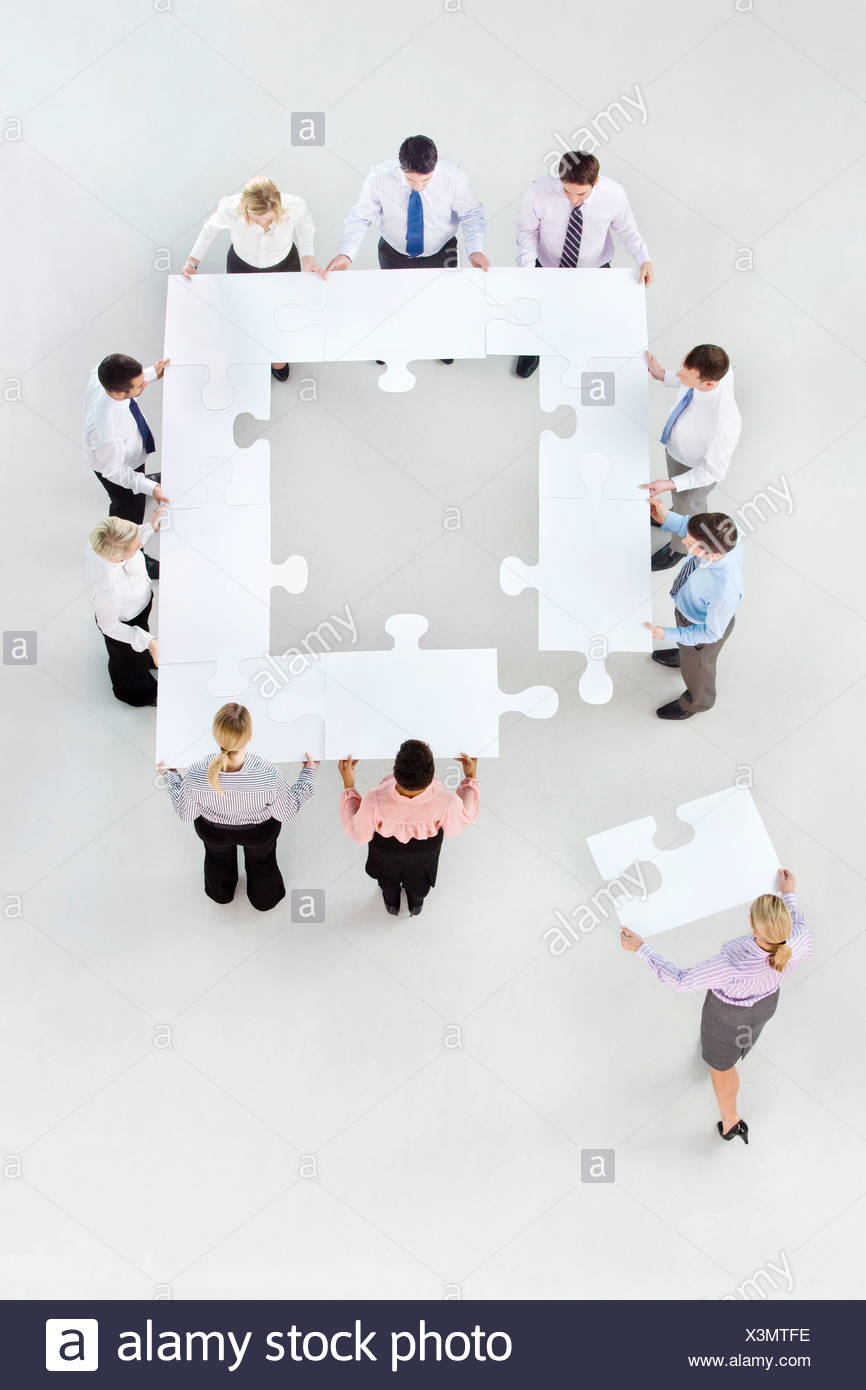 Business people forming square with jigsaw pieces - Stock Image
