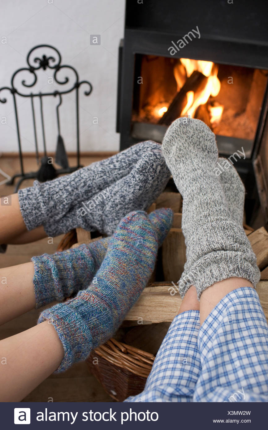 Feet warming by the fireplace - Stock Image