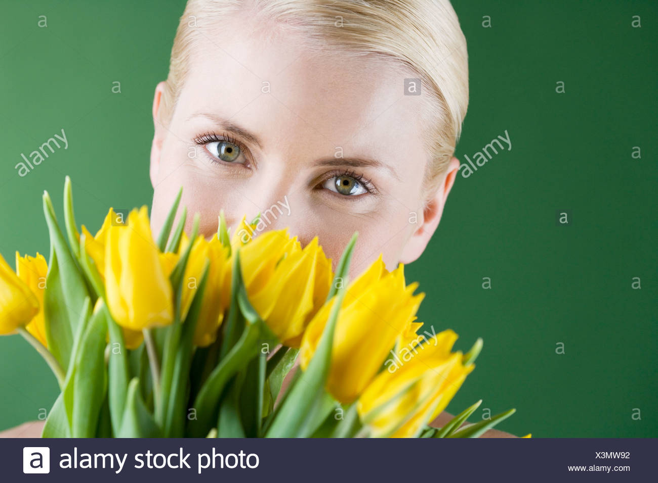 A young blonde woman holding a bunch of yellow tulips - Stock Image