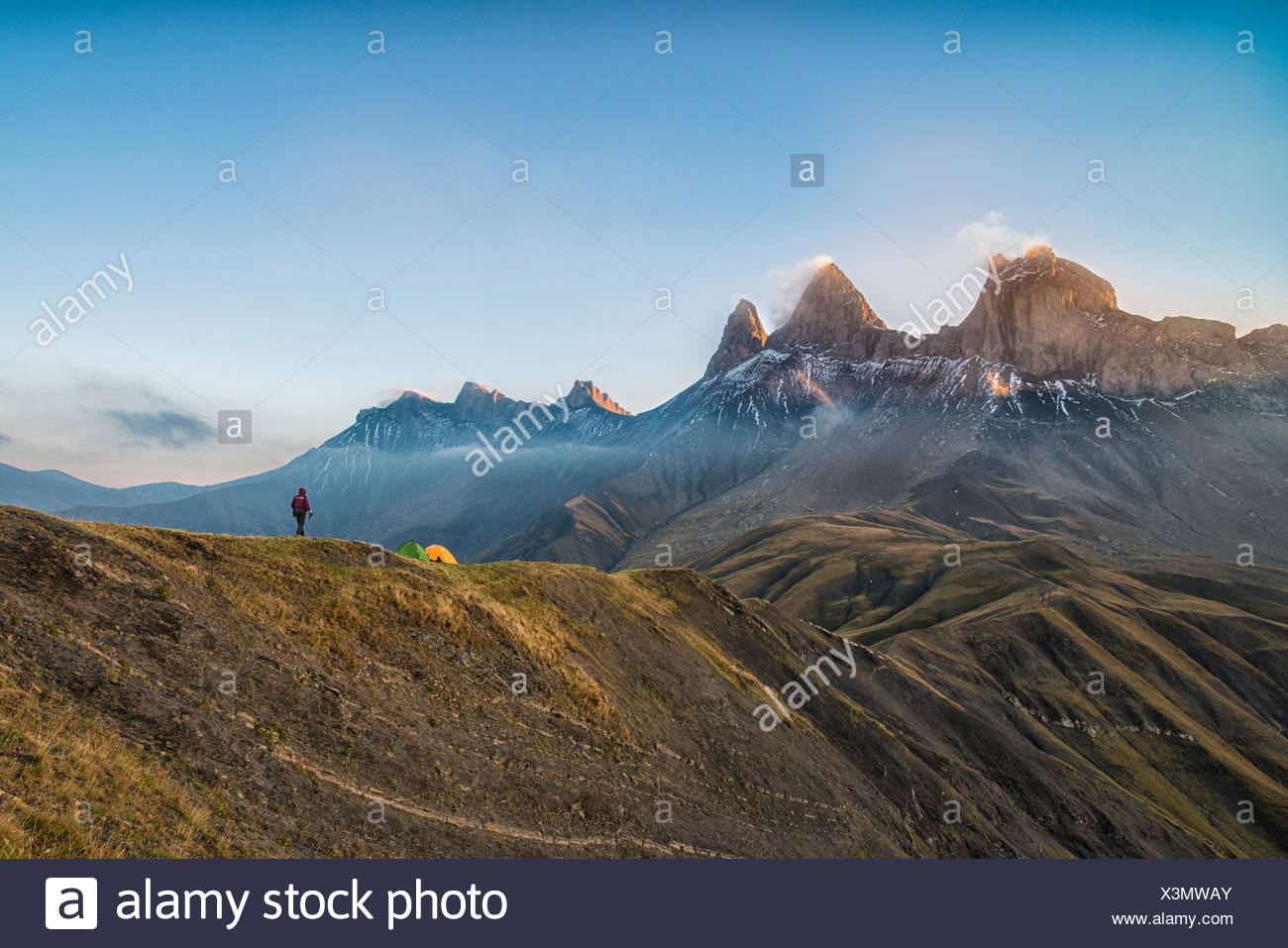 Hiker in front of the Aiguille d'Arves at sunrise, Ecrins, Savoie, France - Stock Image