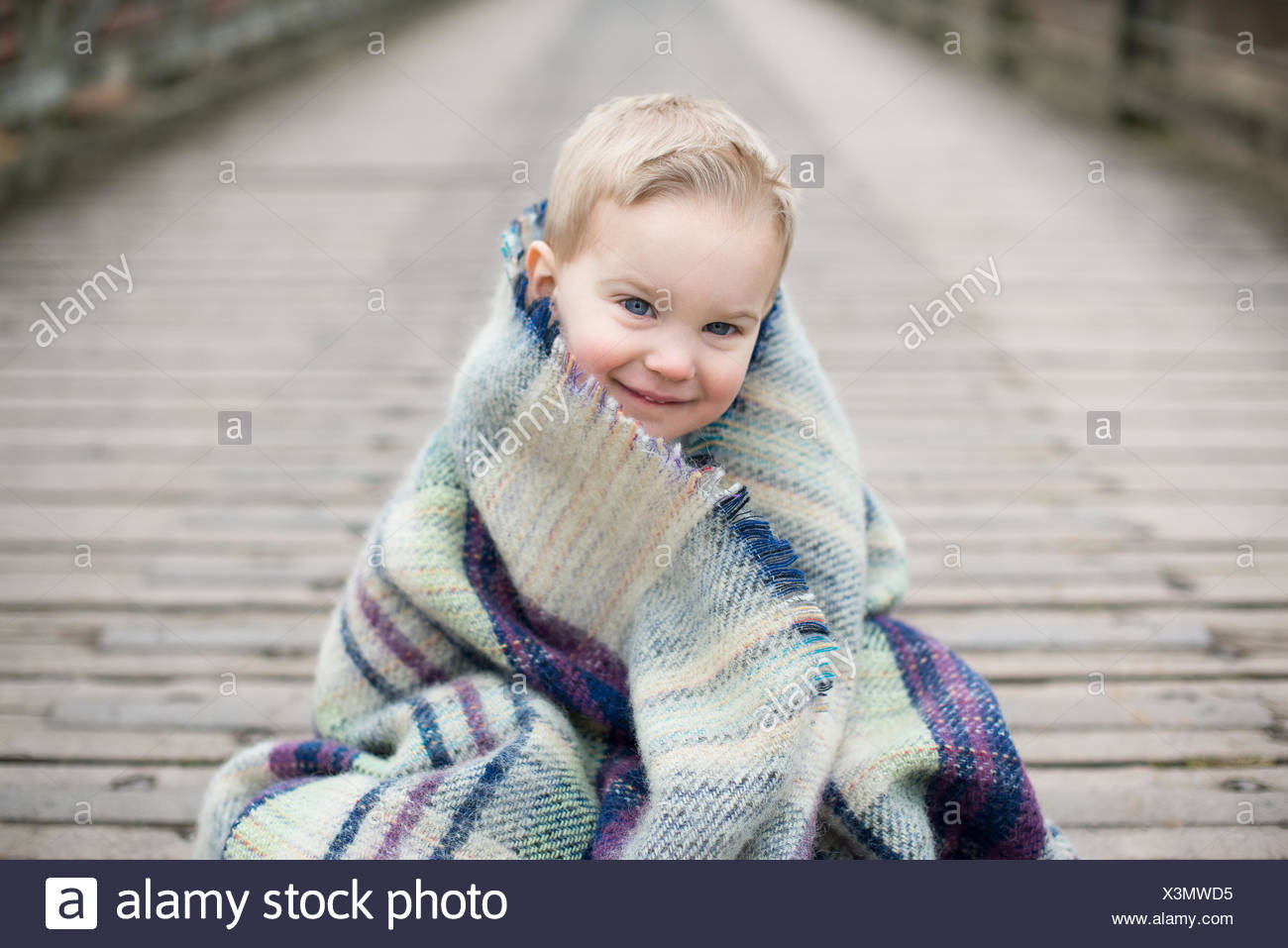 Portrait of a boy wrapped in blanket, sitting on a wooden bridge - Stock Image