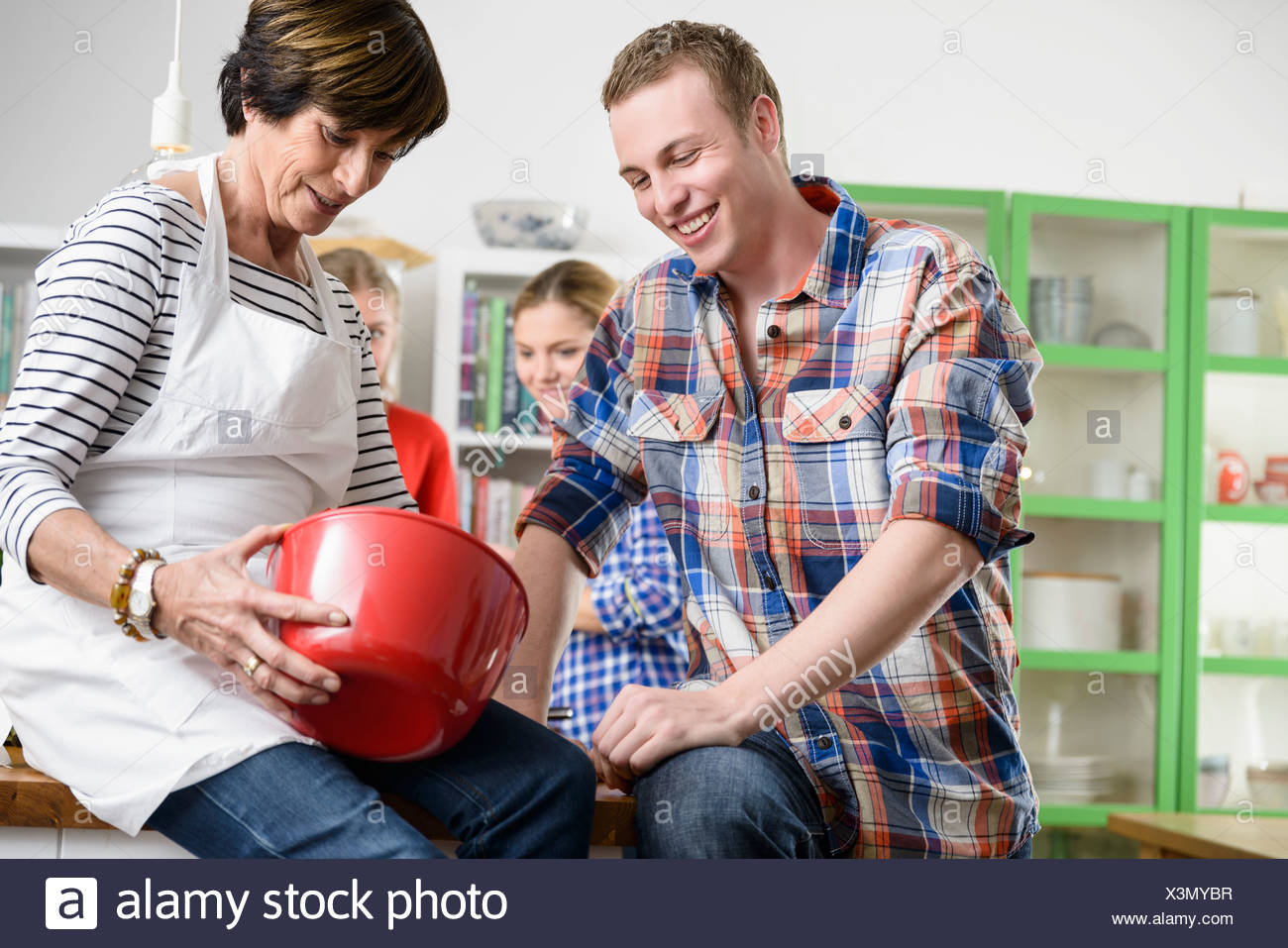 Mother and son looking into red bowl - Stock Image