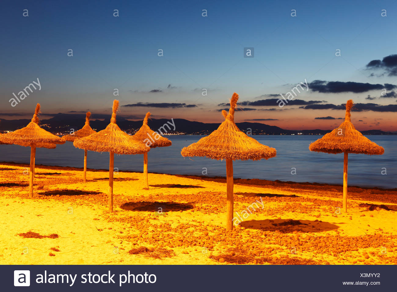 Straw umbrellas on the beach, S'Arenal, El Arenal, evening mood, Majorca, Balearic Islands, Spain, Europe - Stock Image
