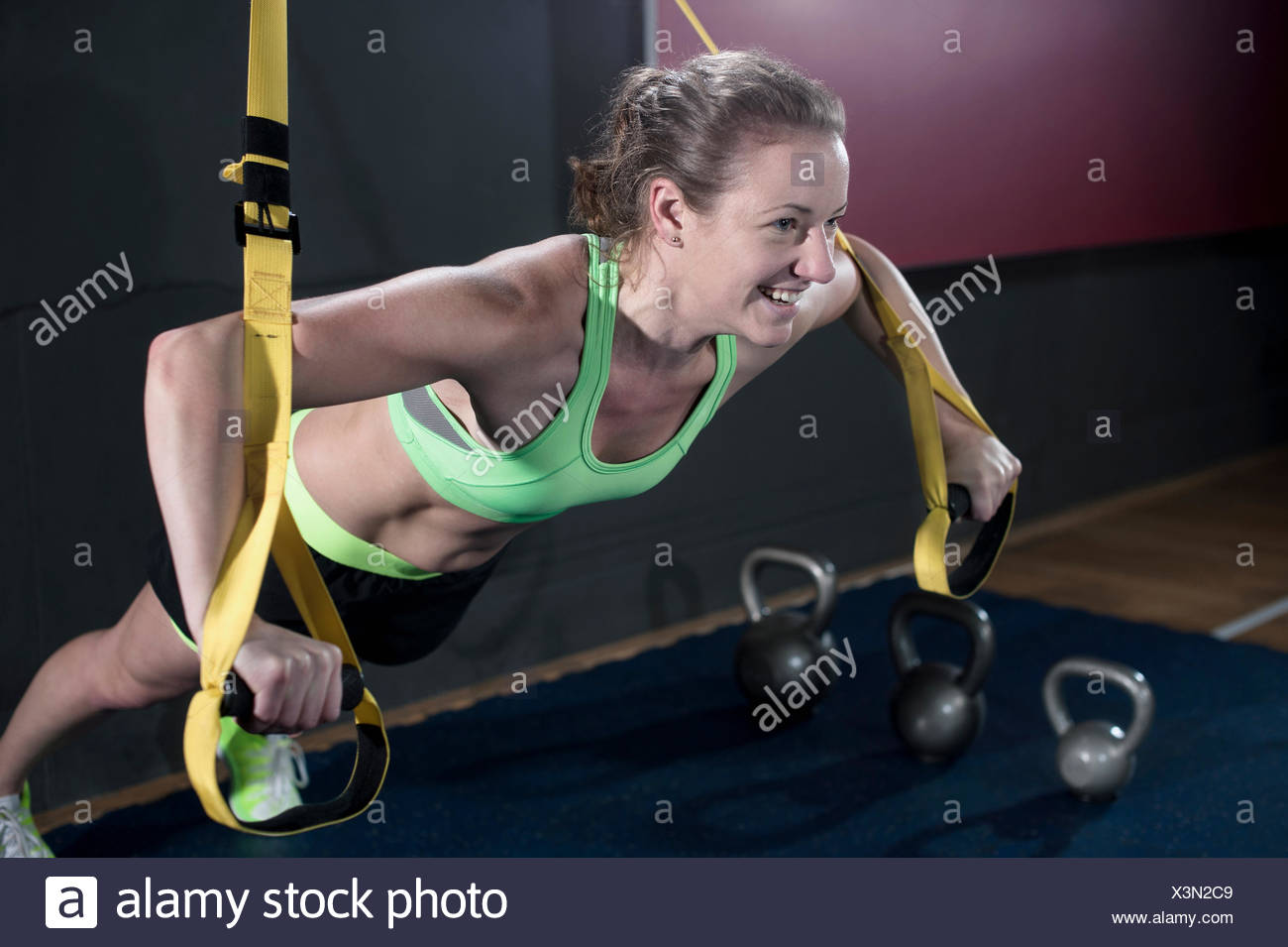 Sportive young woman doing press-ups in the gym with TRX belt, Bavaria, Germany - Stock Image