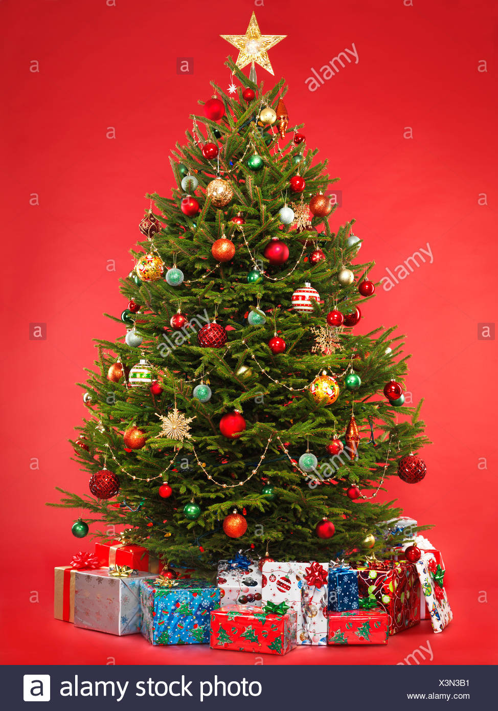 Decorated Christmas tree surrounded with colorful gifts - Stock Image