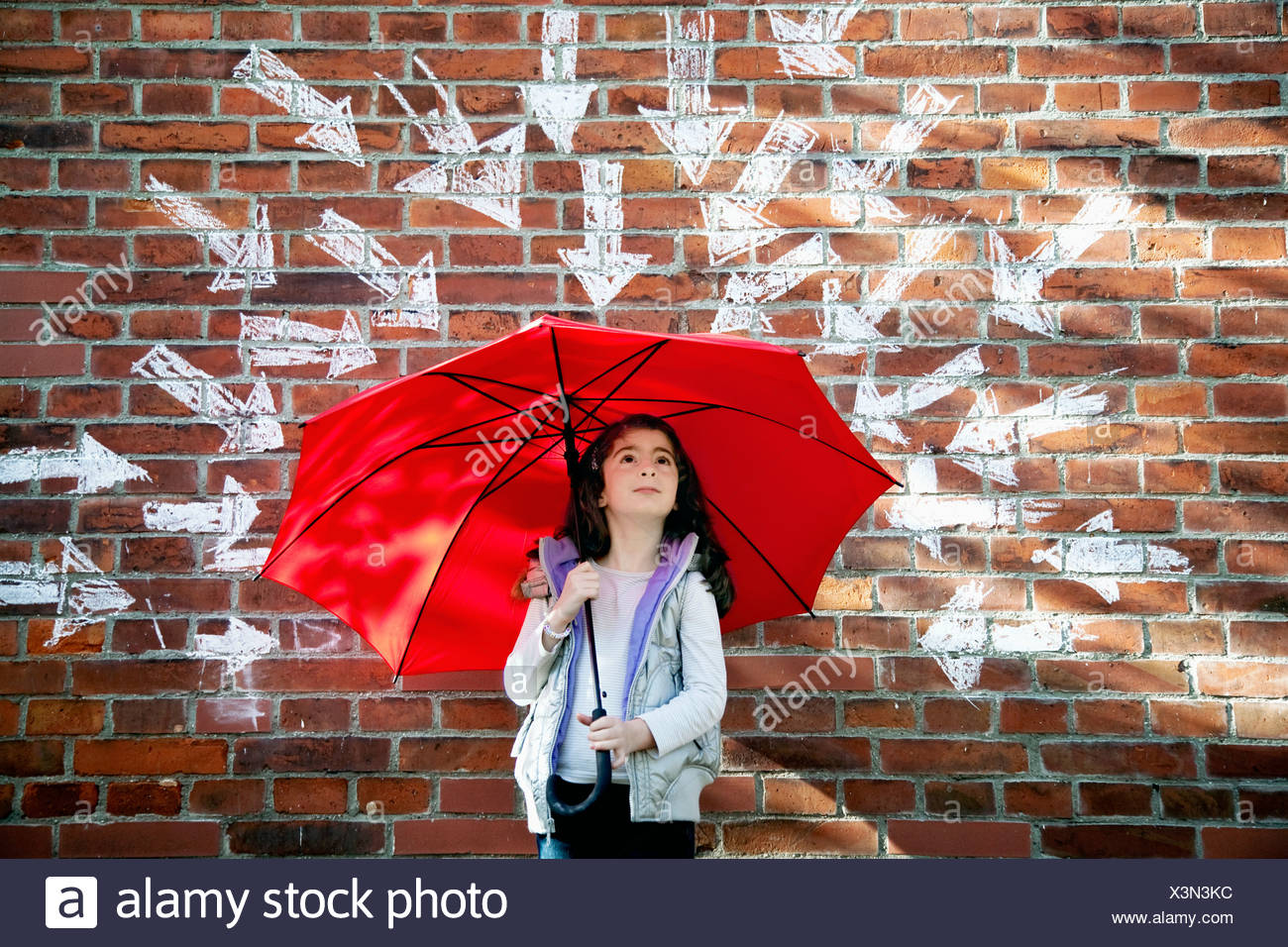 young girl with red umbrella in front of brick wall surrounded by arrows Stock Photo