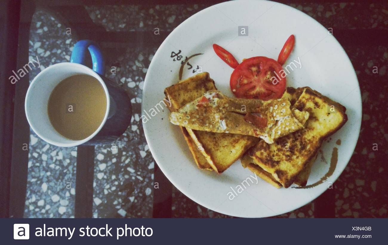 Directly Above Shot Of Sandwich In Plate By Cup Of Tea On Coffee Table - Stock Image