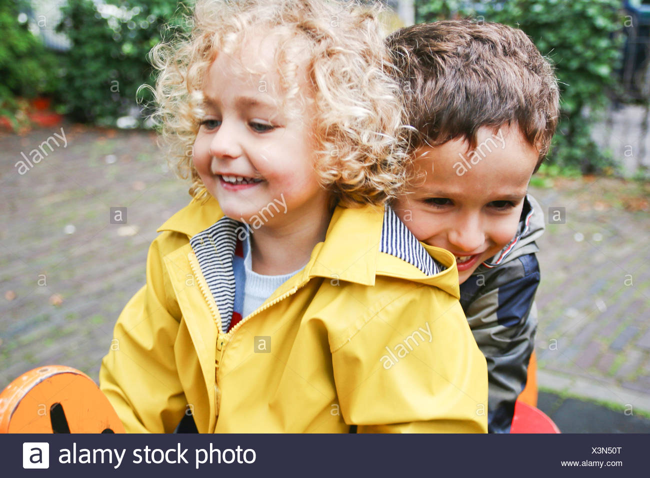 Smiling Boy and girl sitting on spring ride in playground Stock Photo