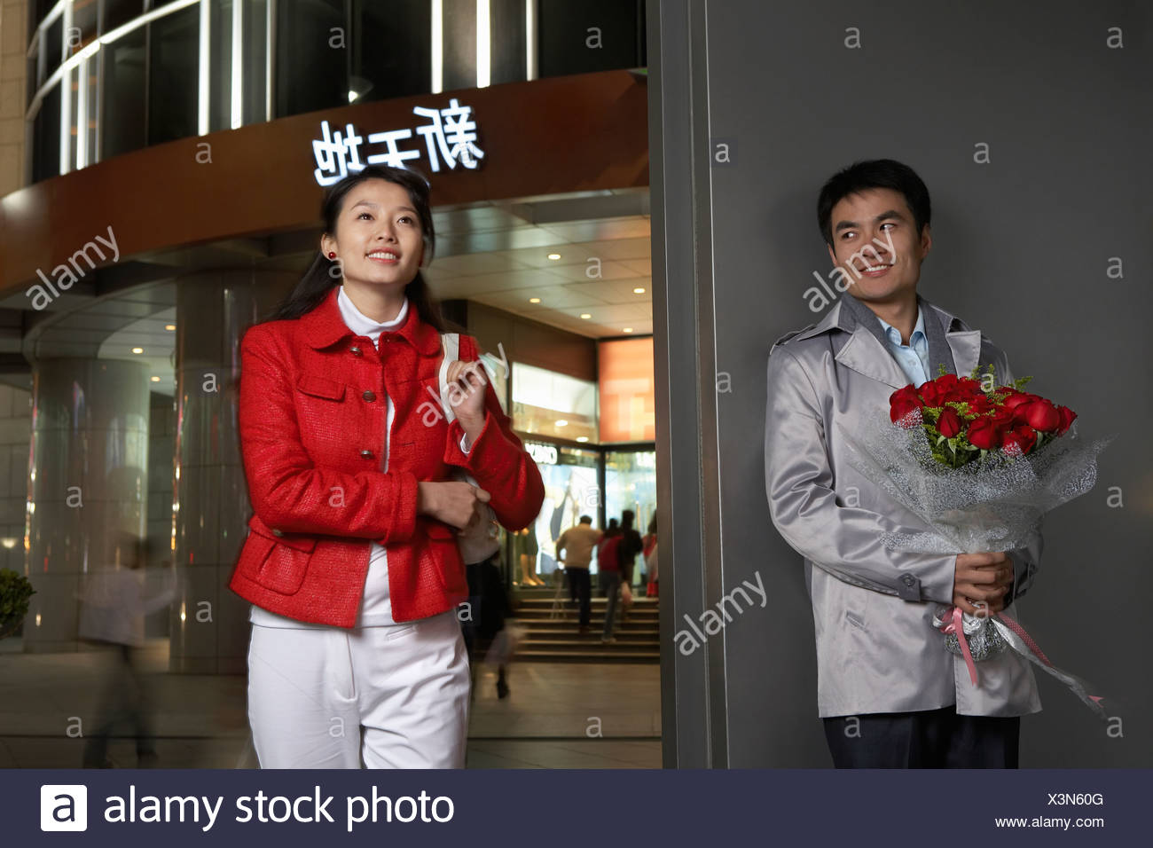 Young Man Holding Bunch Of Flowers And Meeting Girlfriend - Stock Image