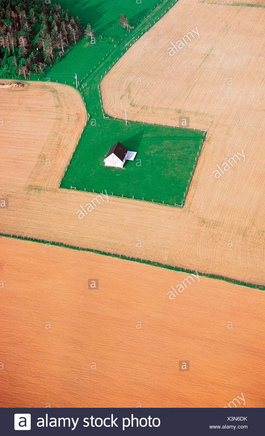 An aerial view of a farmstead surrounded by fields. - Stock Image
