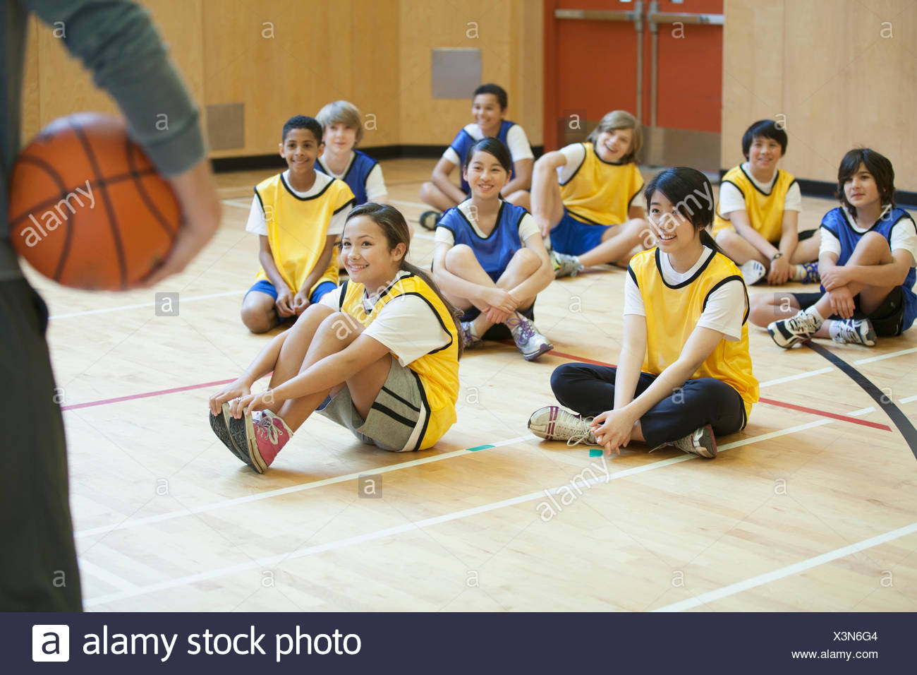 group of middle school students sitting in the gymnasium - Stock Image