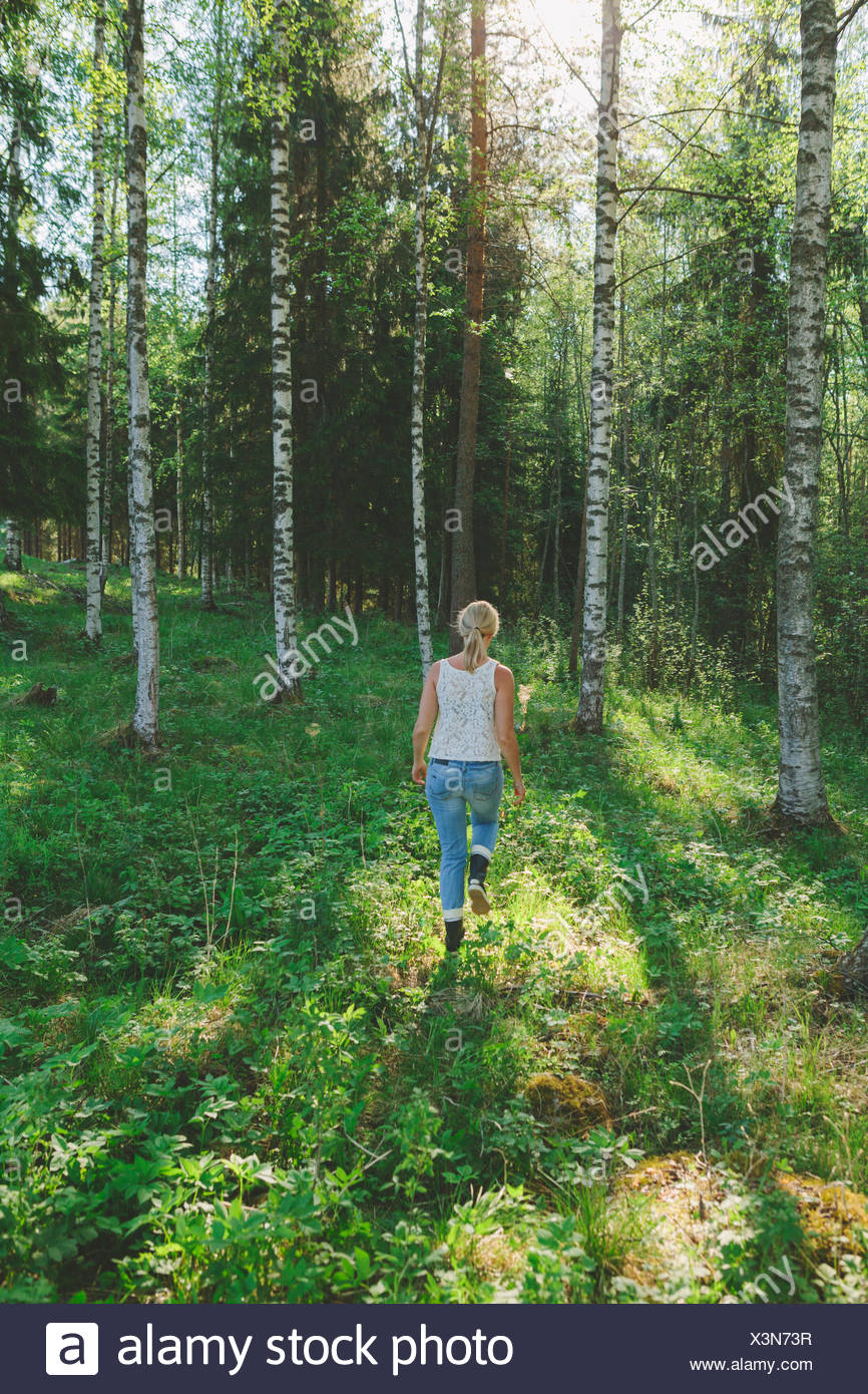 Finland, Mellersta Finland, Jyvaskyla, Saakoski, Woman walking across forest glade Stock Photo