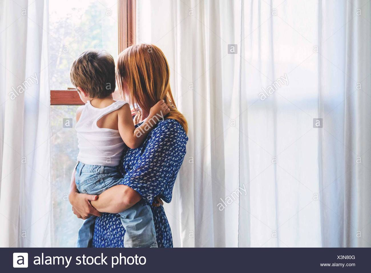 Mother and boy (2-3) child looking out of window - Stock Image