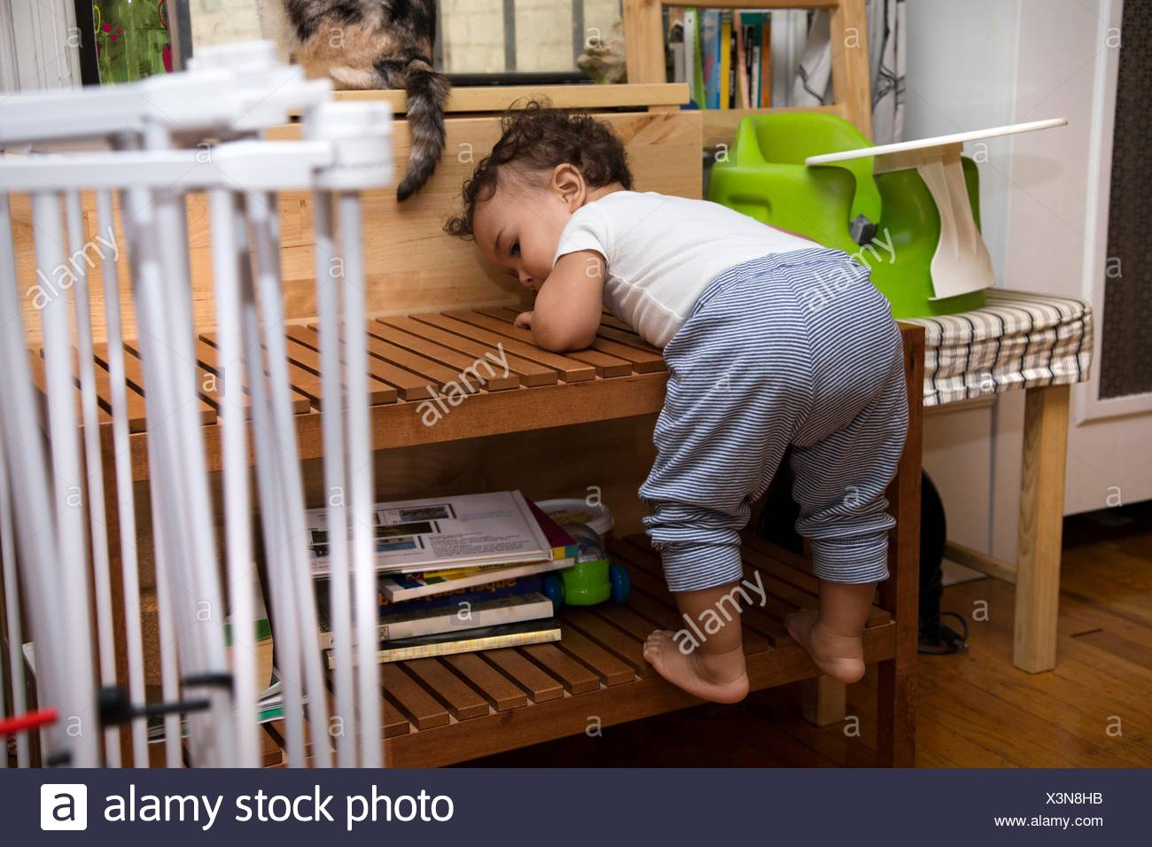 Independent female toddler climbing coffee table in living room - Stock Image