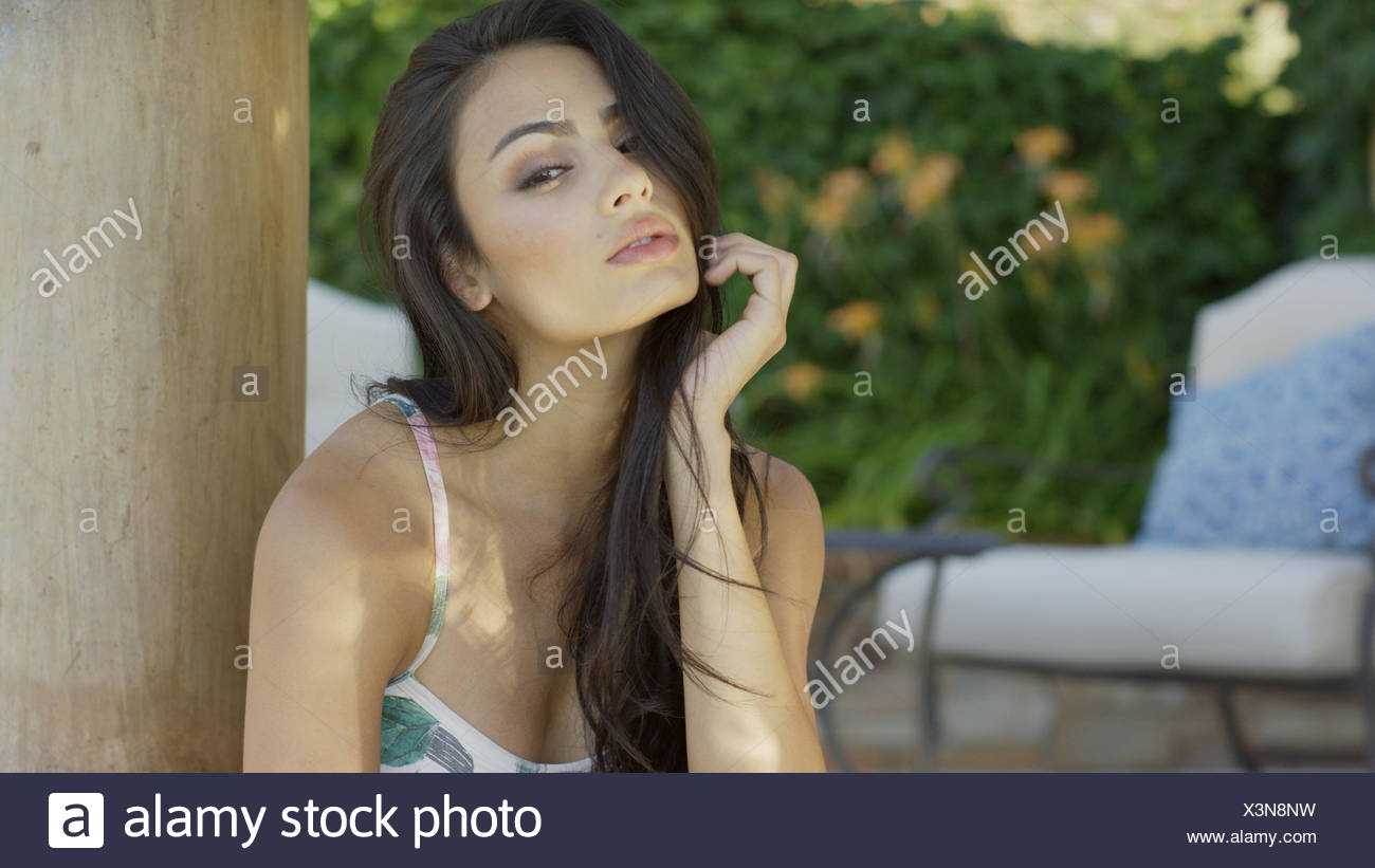 Portrait of sultry woman with long hair wearing swimsuit - Stock Image