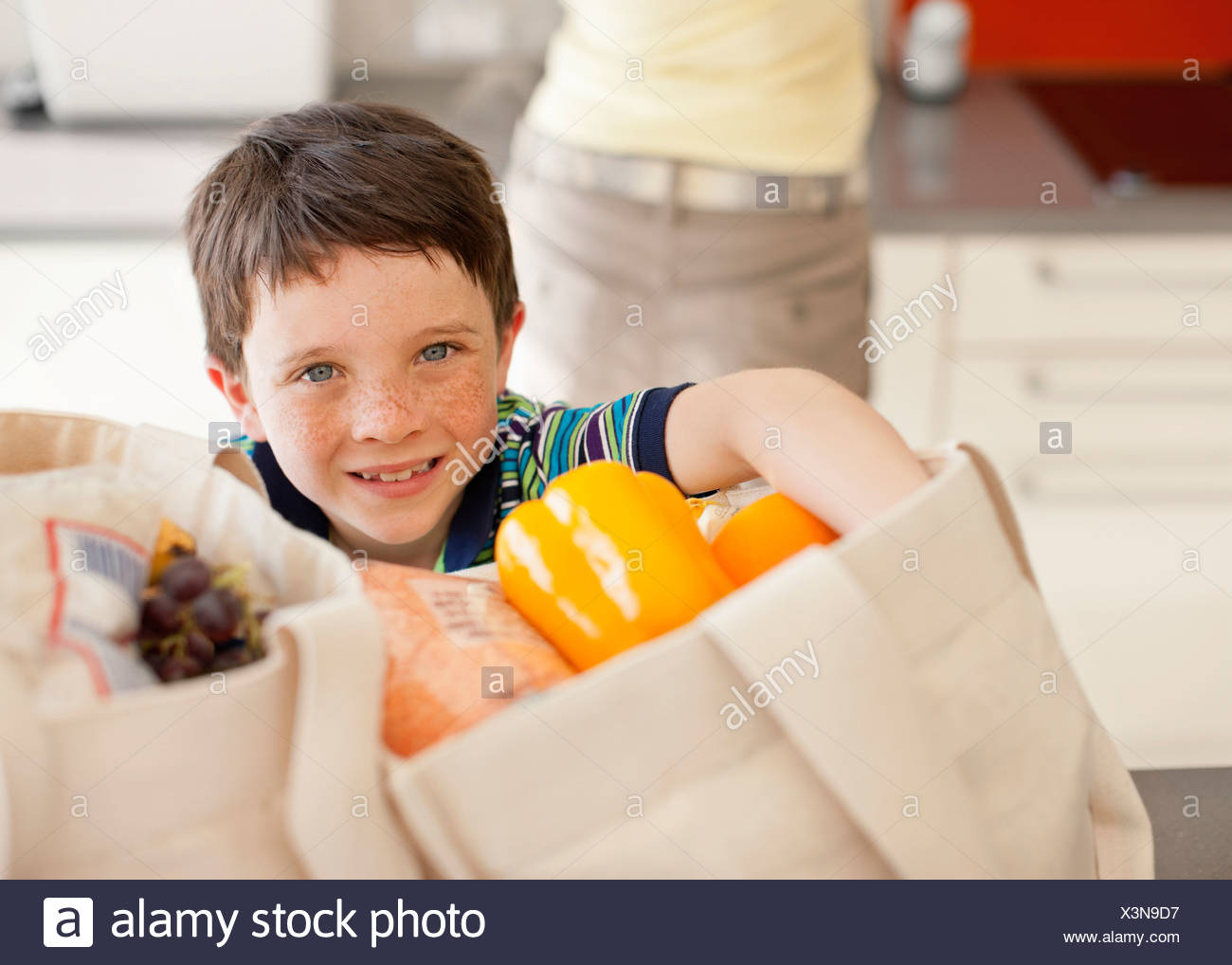 Boy unloading groceries from reusable bag - Stock Image