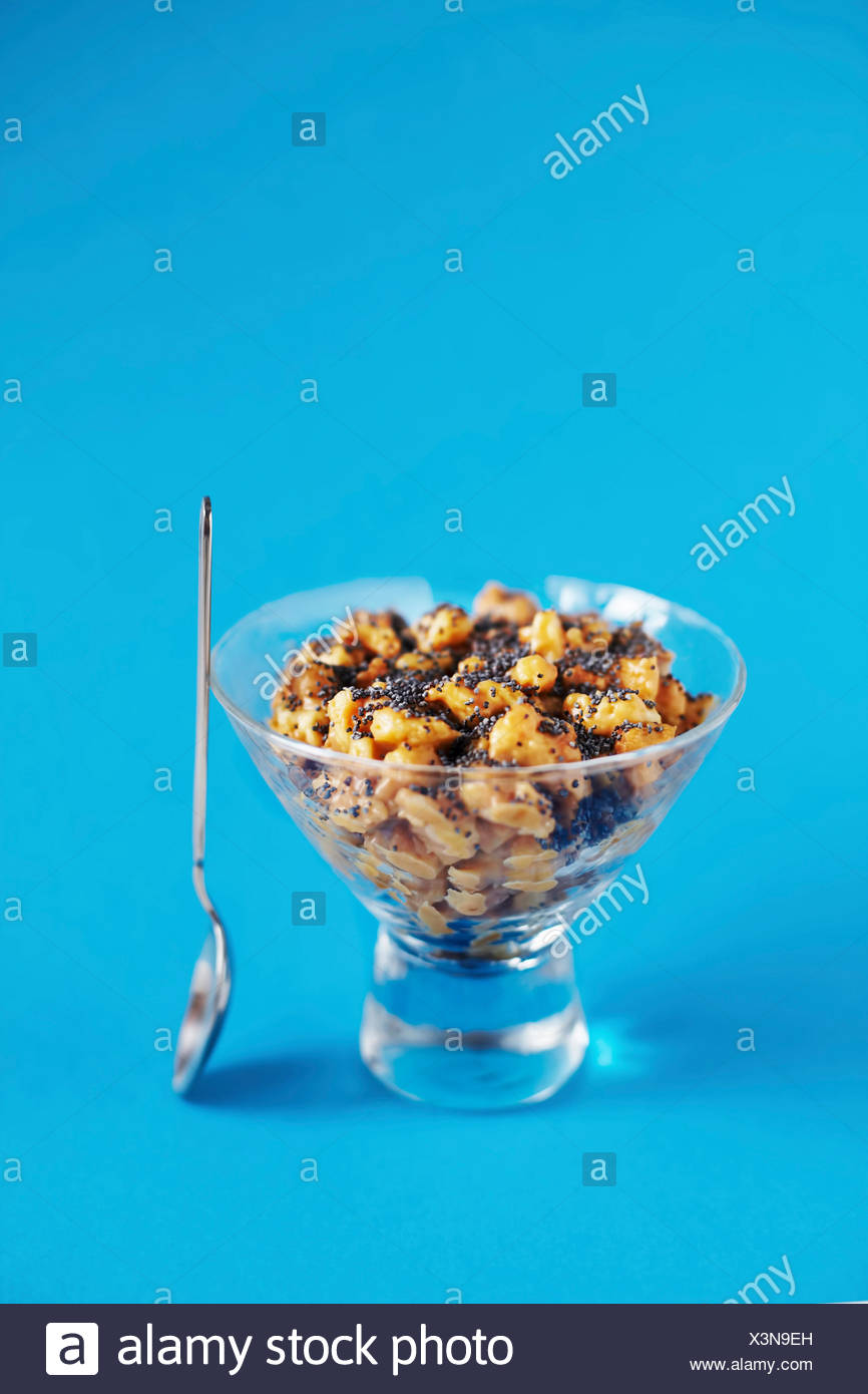 Funnel cake with caramel and poppy seeds on bright blue background - Stock Image